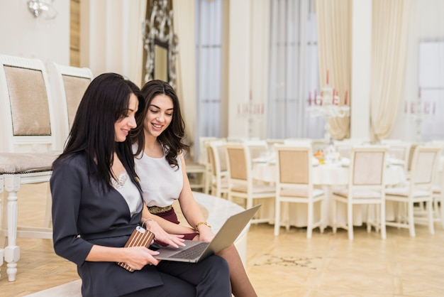Event manager showing something on laptop to woman