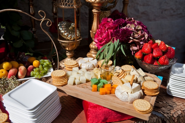 Event reception with appetizers, caviar and crackers, cheese and fruit decorated with flowers