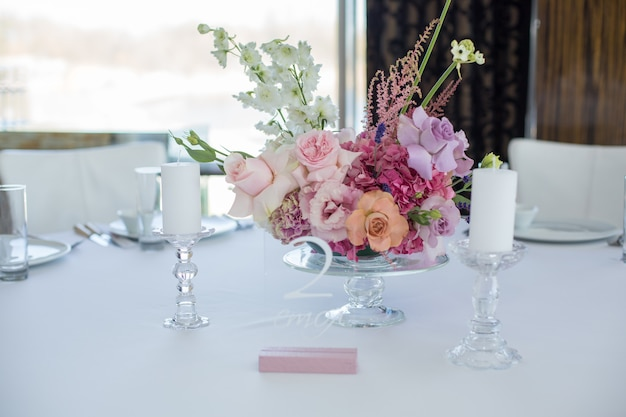 イベント用の白いレストランのテーブルは、繊細な生花で飾られています。