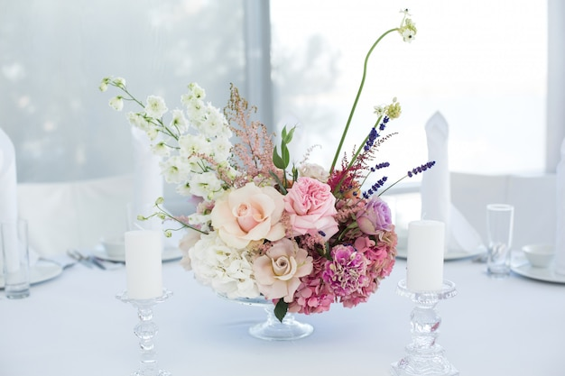 Event white restaurant table served and decorated with delicate fresh flowers
