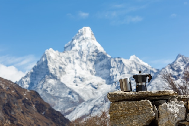 Everest base camp trek. vintage coffee maker with a mug in focus. background of ama dablam is blurred.