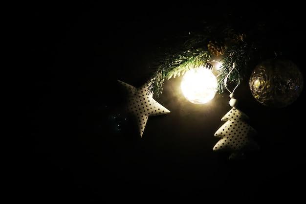 石の背景に常緑樹の手作りおもちゃ、雪片、地球儀、モミの枝、テキスト用のスペースのあるクリスマスグリーティングカード