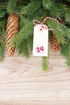 Вечнозеленое дерево с шишками и новогодним ярлыком на 24 декабря