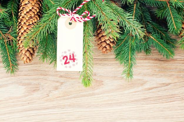12月24日のコーンとクリスマスタグ付きの常緑樹