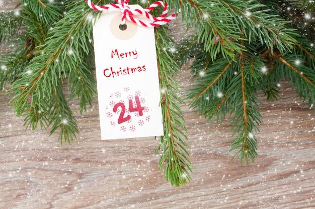 Вечнозеленое дерево с тегом счастливого рождества на 24 декабря