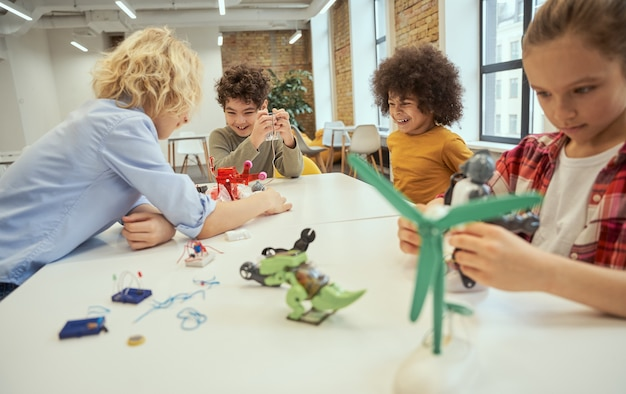 Вечная обучающая группа веселых детей, обсуждающих и исследующих технические игрушки сидя