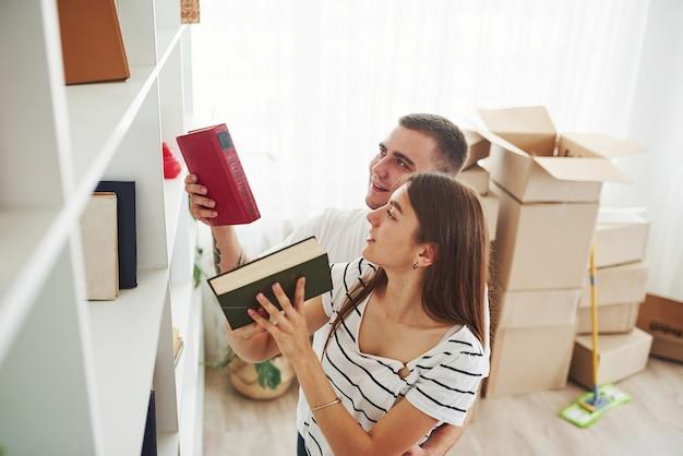 すべての本は正しい場所になければなりません。彼らの新しいアパートで陽気な若いカップル。移動の概念。