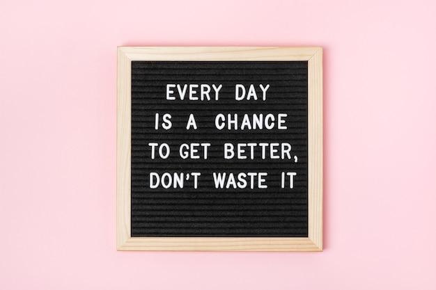 매일이 더 나아질 수 있는 기회입니다. 낭비하지 마세요. 분홍색 배경에 검정 편지판에 동기 부여 인용문. 오늘의 개념 영감 따옴표. 인사말 카드, 엽서입니다. 프리미엄 사진