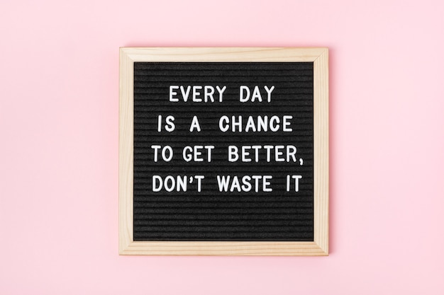 Every day is a chance to get better, don't waste it. motivational quote on black letter board on pink background. concept inspirational quote of the day. greeting card, postcard.