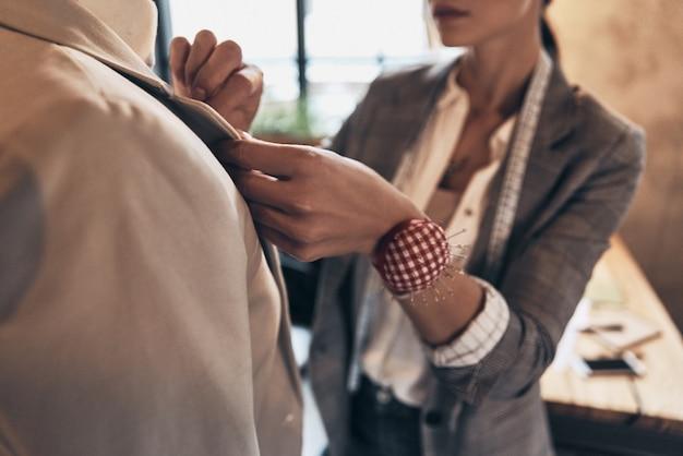 Каждая деталь должна быть безупречной. крупным планом молодая женщина поправляет воротник куртки на манекене, стоя в своей мастерской