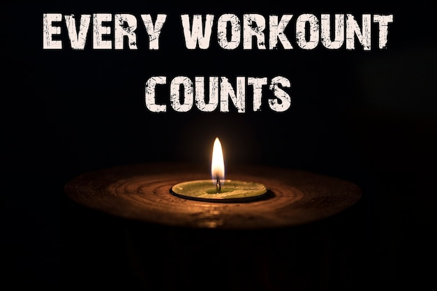 Every workount counts - white candle with dark background - in a wooden candlestick.