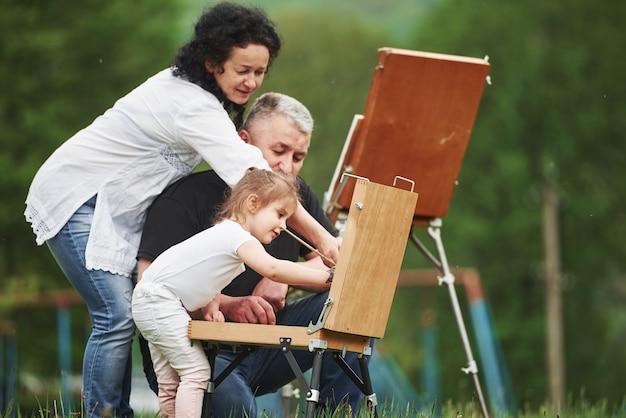 誰もが進行中です。祖母と祖父は孫娘と屋外で楽しんでいます。絵画の構想