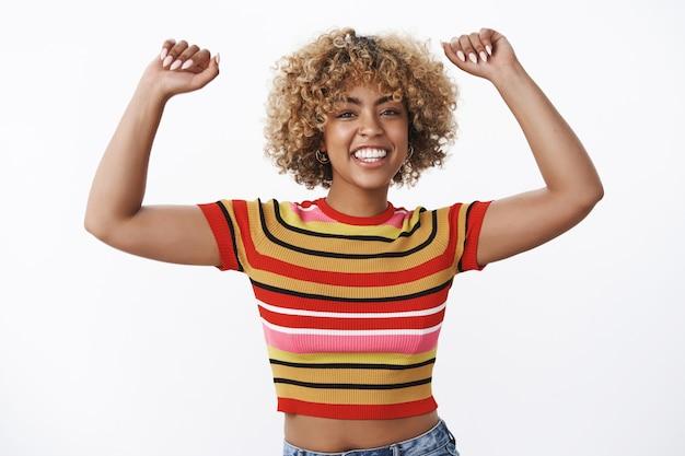誰もがあなたの手を空中に上げます。楽しくてのんきなアフリカ系アメリカ人の少女の肖像画は、腕を高く上げて、白い壁の上で元気と明るい感じで広く笑顔で踊るのを楽しんでいます