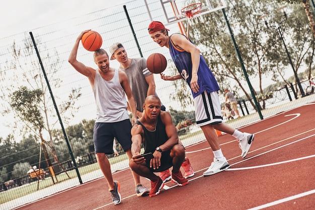 みんな笑顔!スポーツウェアの若い男性のグループは、屋外に立っている間、自分撮りと笑顔を取ります Premium写真