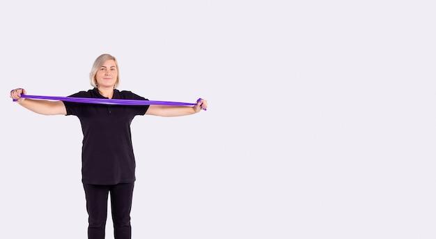 広告のためのスタジオの灰色の背景に自宅で運動する間、ゴム製の抵抗バンドを保持している黒いスポーツウェアのスポーティな年配の女性の高齢者の日常の健康トレーニングボディゴールコンセプト
