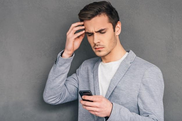日常の問題。携帯電話を持っている物思いにふける若い男