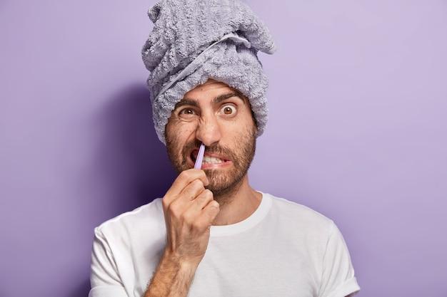 Vita quotidiana e concetto di coccole. close up ritratto di giovane uomo coglie i capelli dalla narice con una pinzetta, soffre di dolore