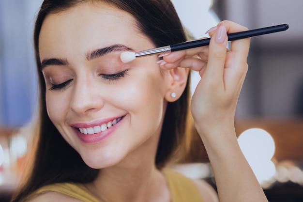 Повседневный макияж. приятная улыбающаяся визажистка с радостью завершает свой повседневный макияж