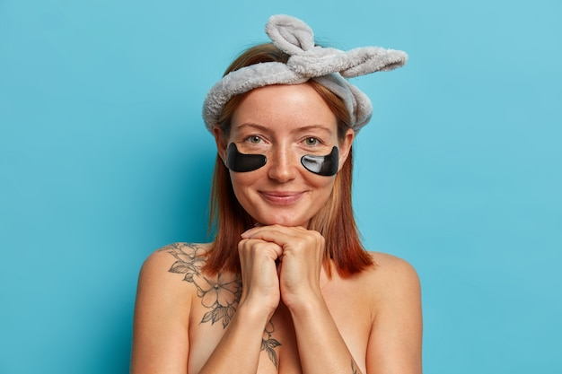 일상 생활. 아름다운 빨간 머리 여자는 턱 아래에 손을 유지하고, 눈 아래에 콜라겐 패치를 착용하고, 건강한 피부를위한 정기적 인 회춘 치료를 받고, 활 헤어 밴드를 착용하고, 맨 어깨를 서 있습니다.