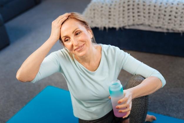 毎日のトレーニング。トレーニング後に水を飲みながら疲れて額をこすりながらスポーティーなフィットの女性