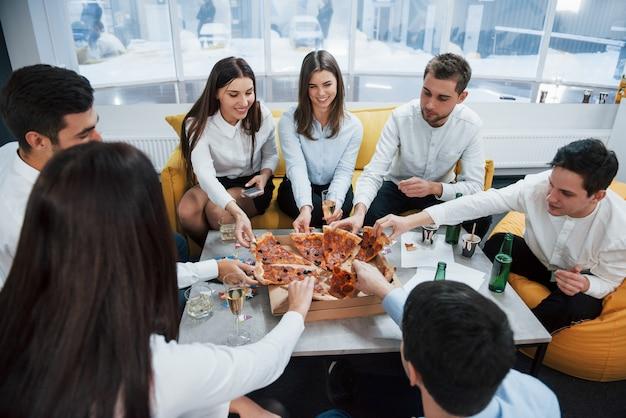 누구나 자신의 슬라이스를 얻습니다. 피자 먹기. 성공적인 거래를 축하합니다. 알코올로 테이블 근처에 앉아 젊은 직장인