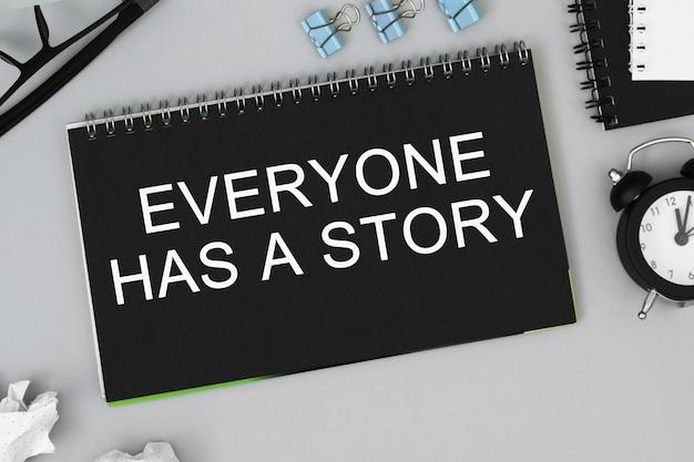 У каждого есть история. канцелярские товары, будильник, блок с текстом. бизнес, концепция образования. плоская планировка