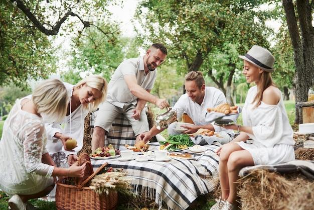 Каждый занят своими делами. группа взрослых друзей отдыхает и беседует во дворе ресторана во время обеда