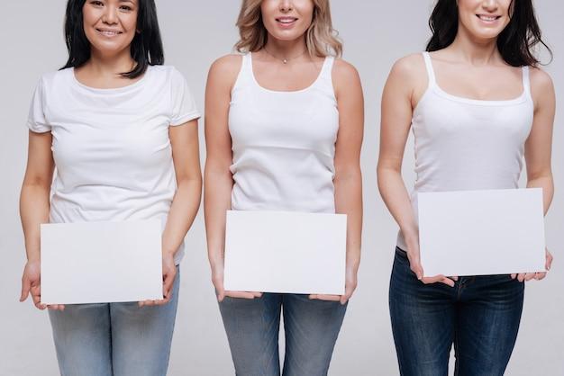 Каждый способен. уверенно улыбающиеся милые женщины, пропагандирующие женственность и разнообразие, позируют с белыми знаками и в одинаковой одежде