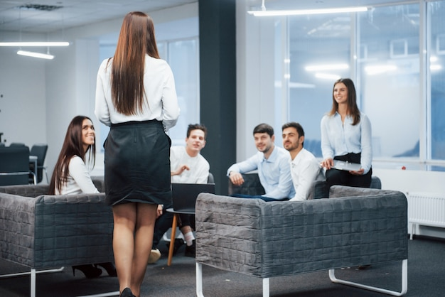 誰もが彼女を喜ばせています。ソファに座って待っている従業員に女の子が歩いている
