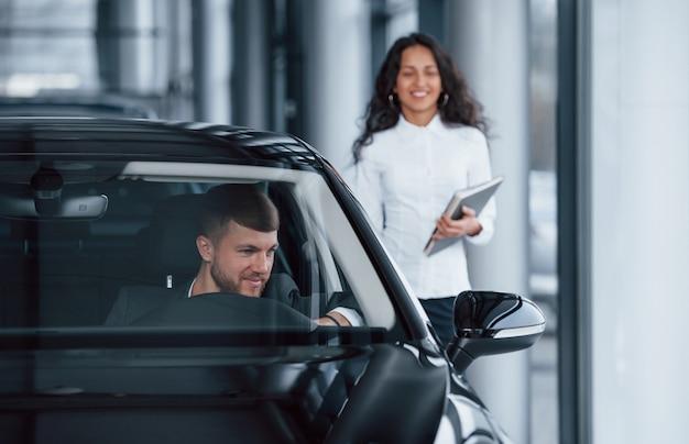 Tutti sono soddisfatti. cliente maschio e donna di affari moderna nel salone dell'automobile