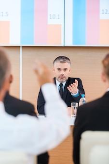 Приглашаем всех к обсуждению. уверенный в себе зрелый мужчина в формальной одежде, говоря слово кому-то из аудитории, сидя в конференц-зале