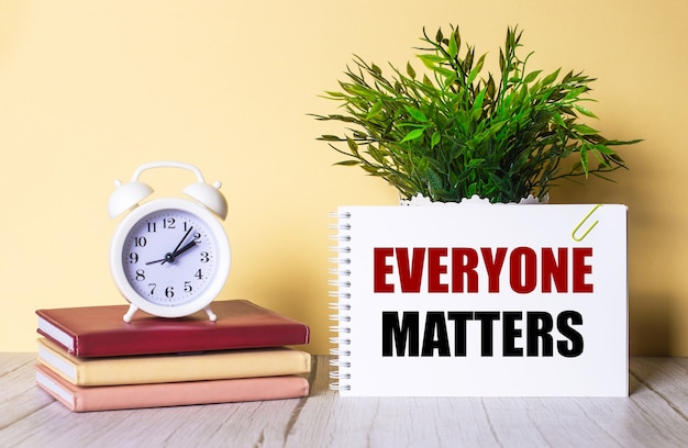 Everyone matters는 녹색 식물 옆에있는 공책과 다채로운 일기에 세워진 흰색 알람 시계에 적혀 있습니다.
