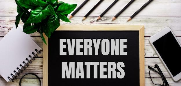 Everyone mattersは、電話、メモ帳、眼鏡、鉛筆、緑の植物の横にある黒い板に白で書かれています