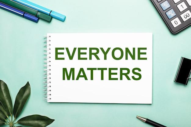 Everyone matters는 편지지와 sheffler 시트 근처의 파란색 표면에 흰색 시트에 기록됩니다. 행동을 요구하다. 동기 부여 개념
