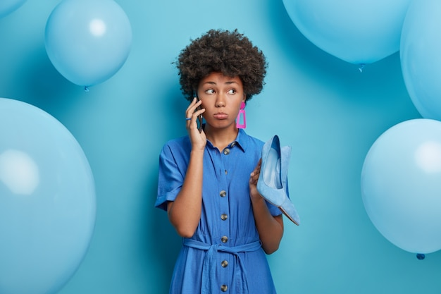 Everything in blue color. sad disappointed afro american woman unhappy about rescheduled party, calls best friend via smartphone, holds fashionable high heel shoes to wear, inflated balloons around.