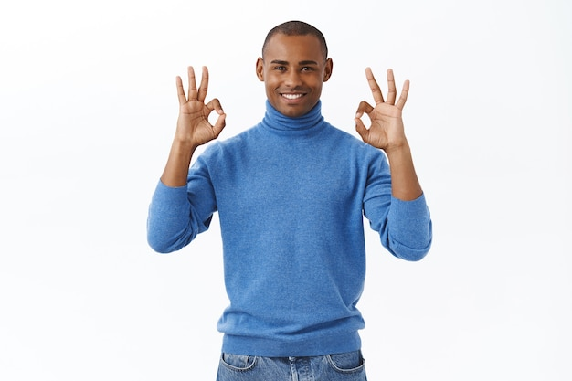 Everything under control. portrait of satisfied, confident african american man smiling, assuring all good, show okay gesture nod agreement