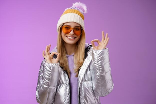 Все хорошо, спасибо. очаровательная кокетливая блондинка уверенная в себе женщина в серебряной стильной куртке, солнцезащитные очки, зимняя шляпа, показывает хорошо, без проблем, хорошо, утвердительно улыбается, любит потрясающий дневной фиолетовый фон.
