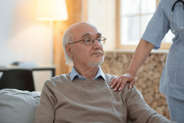 Everything good. upset melancholy senior man sitting while looking aside and doctor putting her hand on his shoulder