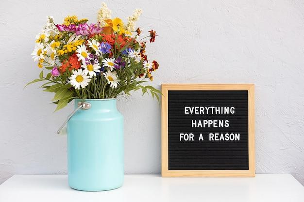 모든 일에는 이유가 있습니다. 편지 보드에 동기 부여 인용 및 회색 돌 벽에 흰색 테이블에 꽃다발 다채로운 꽃. 오늘의 컨셉 영감을 주는 인용문.