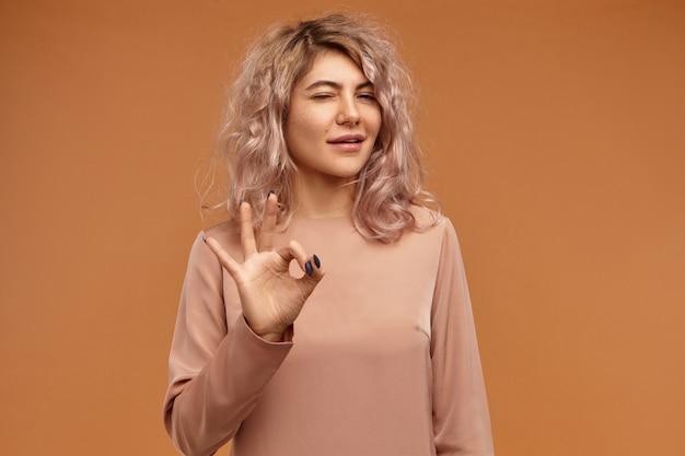 すべてが管理下にあります。親指と人差し指を接続するスタイリッシュな髪型と鼻ピアスを持つ愛らしい自信を持って若いヨーロッパの女性の孤立したショット