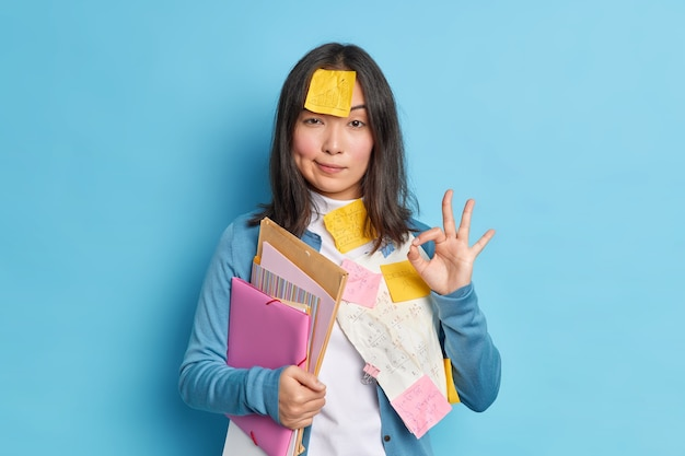 Everything is under control. serious self confident young asian woman makes okay gesture agrees to collaborate with colleague for preparing research work surrounded with papers and stickers.