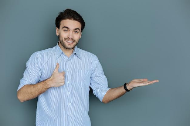 すべてがかっこいいです。素敵な陽気な前向きな男は、素晴らしい気分で笑顔でokジェスチャーを示しています
