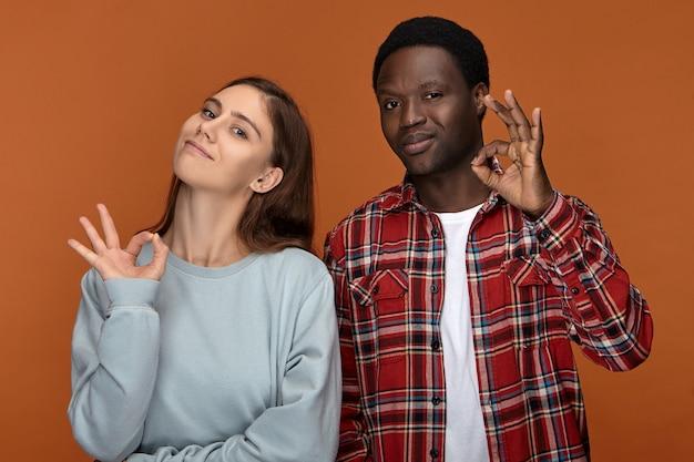 すべて順調。人差し指で親指を回し、笑顔で、良いジェスチャーを示し、相互理解とサポートに大喜びしている機嫌の良い若い異人種間のカップルの肖像画