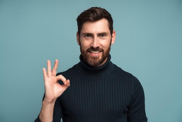 모든 것이 정상입니다. 만족스러운 수염 난 남자 보스는 손가락으로 확인 제스처를 보여주고, 작업을 승인하고, 품질에 만족합니다. 파란색 배경에 고립 된 실내 스튜디오 촬영