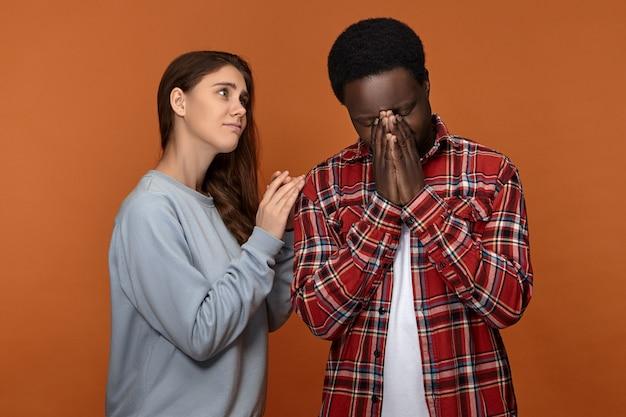 すべてが大丈夫になるだろう。心配している愛情のある若い白人女性が、落ち込んで泣いているアフリカ系アメリカ人の夫を支え、元気づけ、懸念を表明し、肩に手を置いている