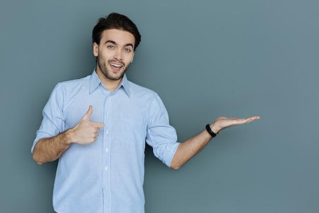 すべてが素晴らしいです。 okジェスチャーを見せながら笑顔であなたを見ているポジティブな素敵な幸せな男