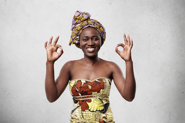 すべて順調です!頭に明るいスカーフを身に着けている美しい陽気なアフリカ女性と彼女の満足度と何かに同意する幸福を示すokサインを示すエレガントなドレス。