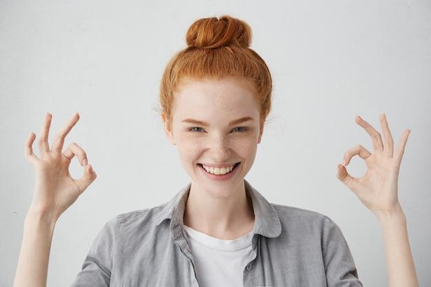 Va tutto bene! allegra eccitata giovane femmina caucasica con nodo di capelli allo zenzero e pelle lentigginosa che mostra il gesto giusto con entrambe le mani e sorride ampiamente, godendosi la sua spensierata vita felice