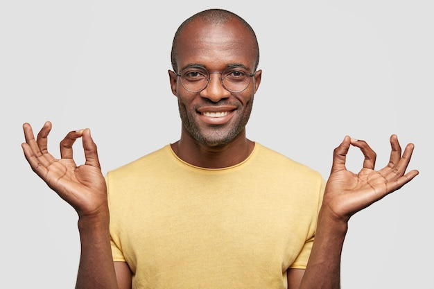 Everything is okay! satisfied bald man with positive smile, gestures indoor, dressed in casual yellow t shirt