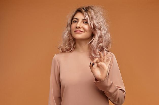 すべてが完璧です。顔のピアスと自信を持って笑顔でボリュームのあるピンクがかった髪の魅力的なかわいい女の子、大丈夫なジェスチャーを作る